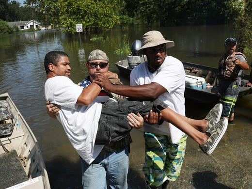 quintin sanders is carried to dry land by volunteer