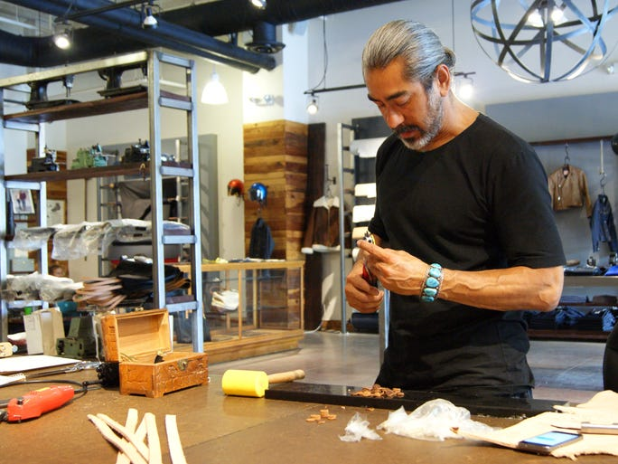 Roman Acevedo, owner of Lawless Denim, handcrafts a leather tote at his store in downtown Phoenix on July 16, 2014.