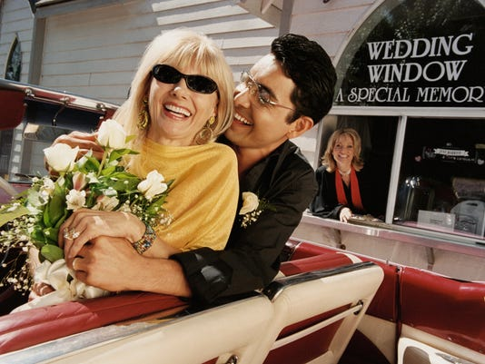 Smiling, Newlywed Couple Sitting in the Front Seat of Their Convertible by a Drive in Church