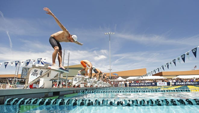 Michael Phelps dives into the pool during the Men's 50-meter freestyle prelims at the Arena Grand Prix on Friday, April 25, 2014 at Skyline Aquatic Center in Mesa.