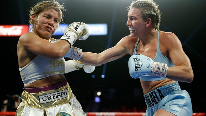 FILE - In this June 15, 2019, file photo, Mikaela Mayer, right, lands a right to Lizbeth Crespo in a boxing match in Las Vegas. Junior lightweight contender Mayer has tested positive for COVID-19 and has been pulled from the co-main event of Las Vegas' first major boxing card since the start of the coronavirus pandemic.