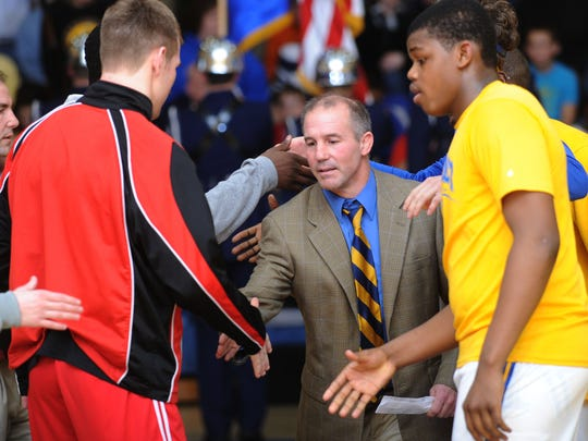 Caesar Rodney head wrestling coach Dickie Howell reaches to shake hands with Smyrna's team captains before a 2013 match.