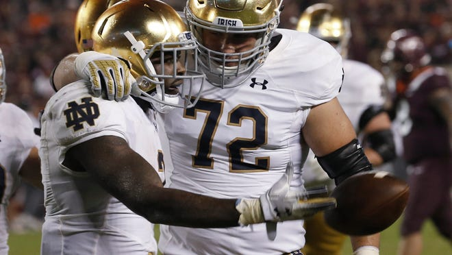 Notre Dame running back Dexter Williams, left, celebrates a touchdown with offensive lineman Robert Hainsey (72) during the second half of an NCAA college football game against Virginia Tech in Blacksburg, Va., Saturday, Oct. 6, 2018. Notre Dame won 45-23. (AP Photo/Steve Helber)