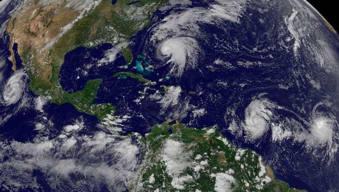 This image made available by the NOAA-NASA GOES Project shows tropical weather systems Hurricane Norma, left, on the Pacific Ocean side of Mexico; Jose, center, east of Florida; Tropical Depression 15, second from right, north of South America, and Tropical Storm Lee, right, north of eastern Brazil, on Saturday, Sept. 16, 2017 at 2:45 p.m. EDT.