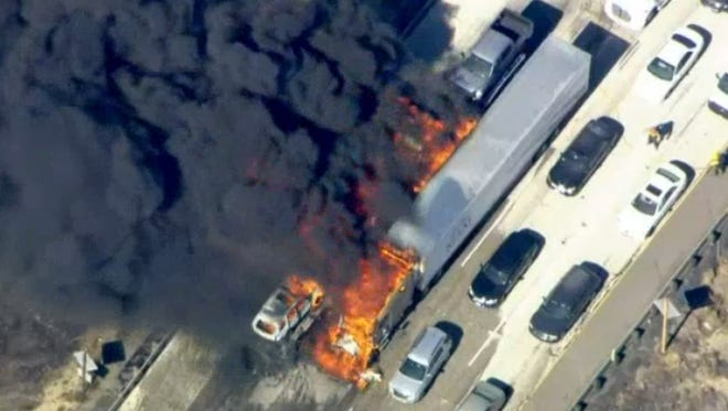 Smoke rises from vehicles as a fast-moving wildfire swept across a freeway Friday, July 17, 2015, near Hesperia, Calif. The fire swept by desert winds burned on both sides of Interstate 15, the main connector between Southern California and Las Vegas that was crowded with vehicles. (NBC4 via AP) MANDATORY CREDIT