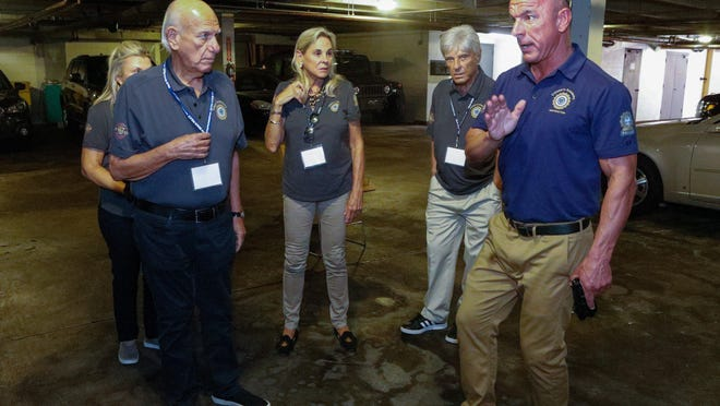 Michael Ogrodnick, right, of the Palm Beach Police Department, teaches Citizen's Academy members how to use the Axon Taser X26P inside the department's garage on Wednesday.
