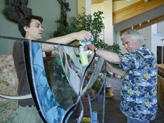 Reeve Tinnell, left, and Dennis Lippert clean a stained-glass