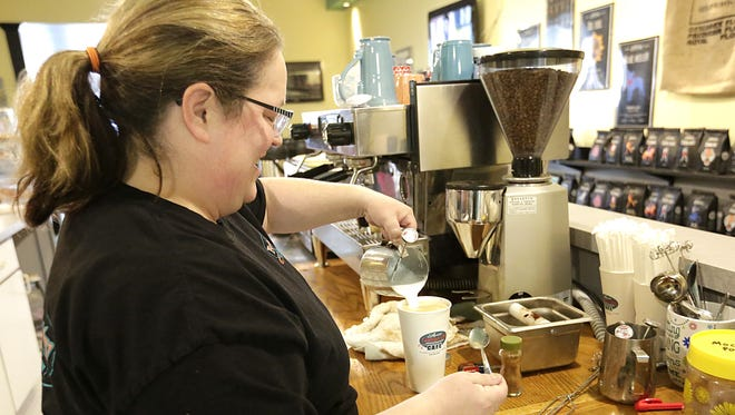Ann Culver, owner of Annie's Fountain City Cafe in downtown Fond du Lac, tops off a drink Tuesday. The business opened Monday.