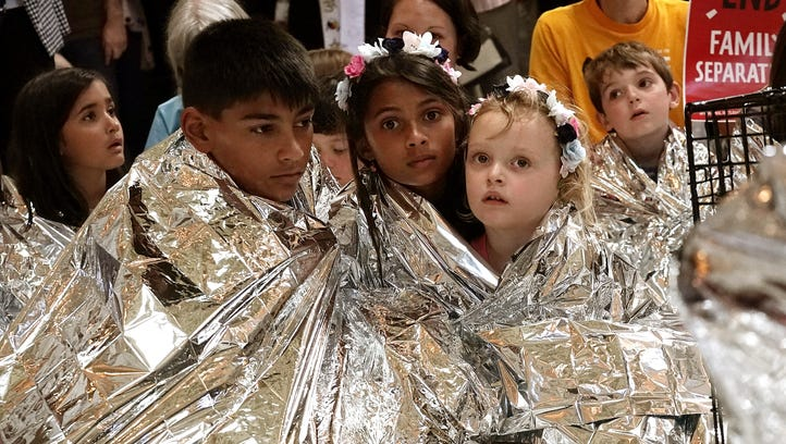 Children wrap themselves up with Mylar blankets to