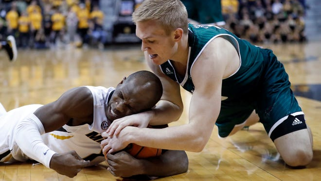 Green Bay's Hunter Crist, right, and Missouri's Terrence Phillips dive after a loose ball during the second half of an NCAA college basketball game Saturday, Dec. 9, 2017, in Columbia, Mo.