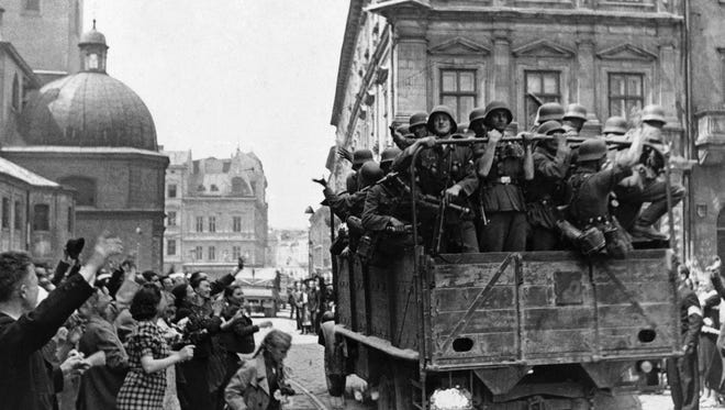 Inhabitants of Lwow  on July 2, 1941, Soviet occupied former Poland wave at a passing truckload of German solders as Nazi; troops took over the city. (AP Photo)