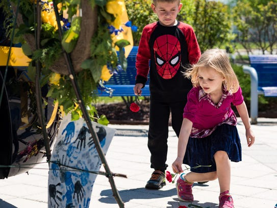 Keene Elementary School students leave flowers and