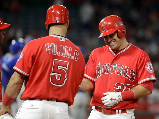 Los Angeles Angels' Mike Trout, right, celebrates his double with Albert Pujols during the seventh inning of a baseball game against the Toronto Blue Jays in Anaheim, Calif., Saturday, April 22, 2017. (AP Photo/Chris Carlson)