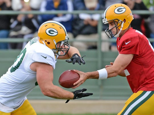 Fullback John Kuhn (30) takes a handoff from quarterback Aaron Rodgers (12) during Green Bay Packers Training Camp at Ray Nitschke Field on Aug. 20.