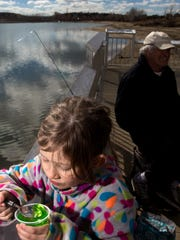 Elizabeth Howerton enjoys a snack while fishing with her grandfather Curtis Howerton, on Monday at Farmington Lake.