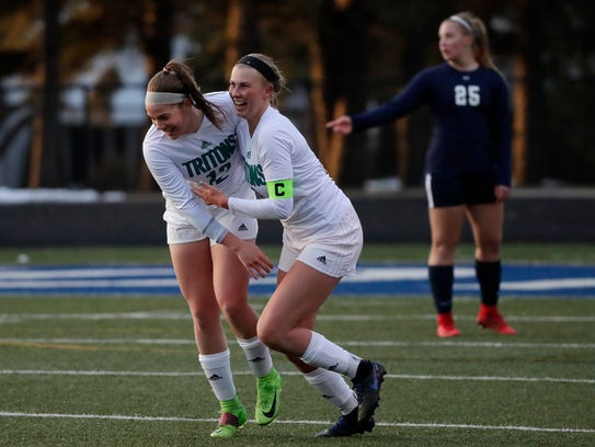 Green Bay Notre Dame's Grace Shaw (6) and Keighley Blindauer (12) celebrate after a goal against Appleton North in an April 10 match.