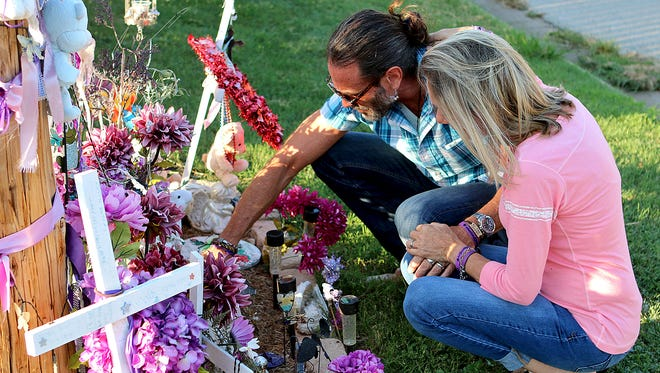Vern and Bianka Landavazo look over mementos left behind at the memorial for their daughter, Lauren Landavazo, on Aug. 28. Lauren was murdered on Sept. 2, 2016.