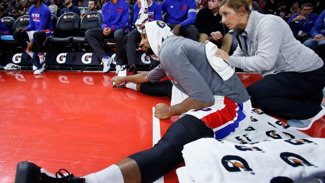 Pistons' Andre Drummond receives help stretching from assistant athletic trainer Jessica Schaefer during the first half of the 118-114 loss to the Hak