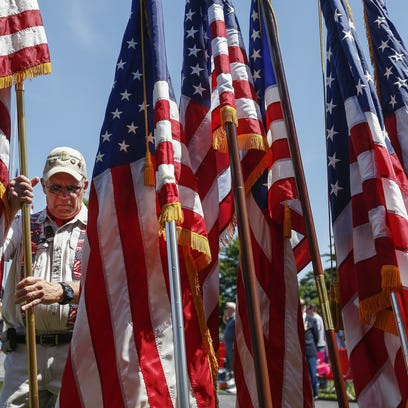 Vietnam veteran Rex Krasche posts the U.S. flag during
