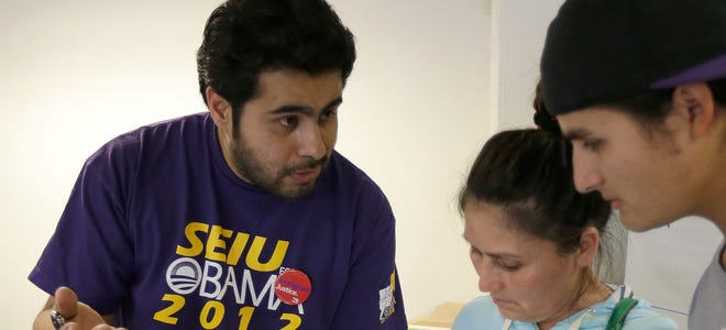 SEIU-UHW worker Carlos Castaneda, left, speaks with Maria Villanueva and Luis Cisneros, of Oakland, Calif., regarding their enrollment in the Affordable Care Act on March 27 in San Francisco.