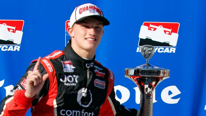 Sage Karam poses with the Indy Lights championship trophy at Auto Club Speedway on Oct. 19.