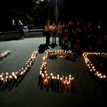 Candles are left during a vigil at Stewart Park in Roseburg, Ore., on Thursday, Oct. 1, 2015. Students, families and supporters gathered after a shooting at Umpqua Community College.