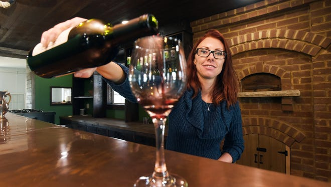Camieo Adams pours a glass of wine at Vinberige Vineyards in Thornville. Adams, her husband Bryan and business partner Patrick Grapevine have transformed the Adam's family farm into an entertainment venue.