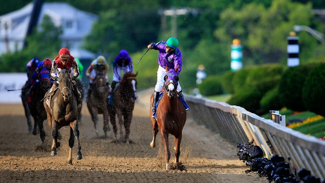 California Chrome, ridden by Victor Espinoza, crosses the finish line to win the 139th running of the Preakness Stakes at Pimlico Race Course on May 17 in Baltimore, Maryland.