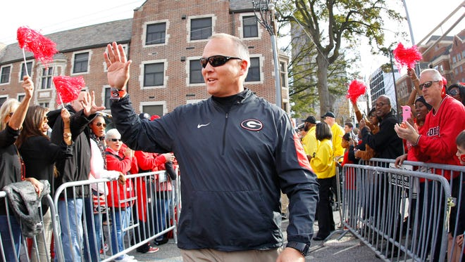 "Georgia head coach Mark Richt greets the crowd during the ""Dog Walk"" as he and his team arrive for a game against Georgia Tech Saturday. Georgia fired Richt Sunday after 15 seasons at the school."
