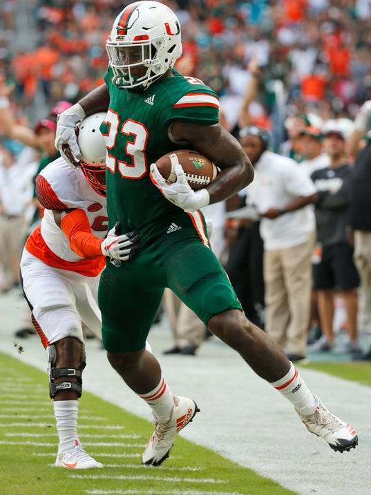 Miami tight end Christopher Herndon IV (23) is pushed out of bounds by Syracuse defensive back Juwan Dowels during the first half of an NCAA College football game, Saturday, Oct. 21, 2017 in Miami Gardens, Fla. (AP Photo/Wilfredo Lee)