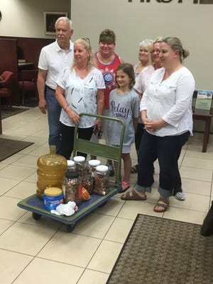 Family and supporters of Sallye Carnes Creech gather for a photo with the approximately $700 in pennies collected for the American Cancer Society.