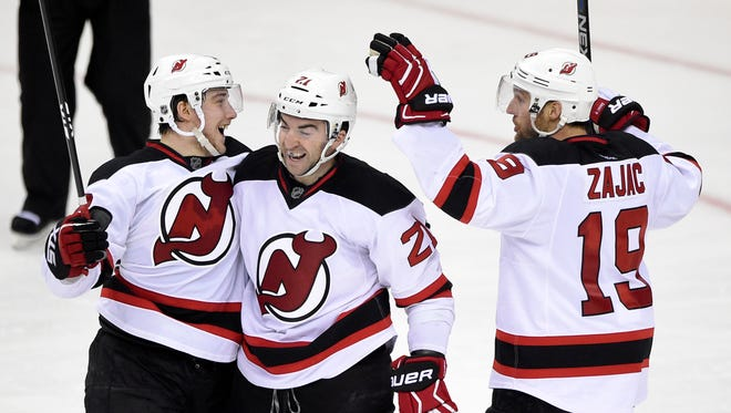 New Jersey Devils center Reid Boucher, left, celebrates his goal with right wing Kyle Palmieri (21) and center Travis Zajac (19) during a game last season.