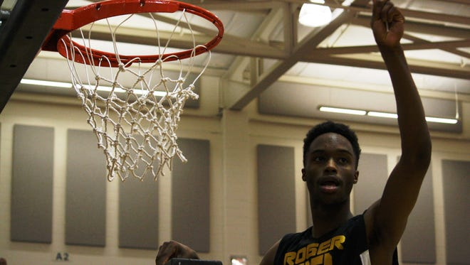 Roger Bacon senior Carlas Jackson cuts down the net after the Spartans beat Summit Country Day in the Division III regional finals.