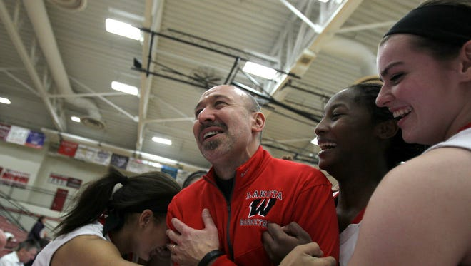 The Lakota West girls basketball team congratulates head coach Andy Fishman on his 300th career win after defeating Fairfield 70-21, Wednesday.
