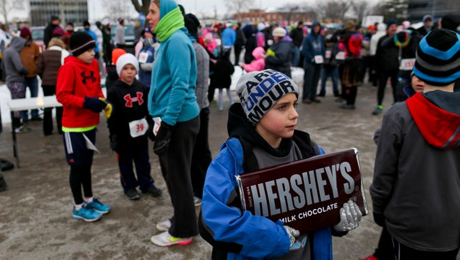 Hunter Hansen, of Marysville, holds a five-pound chocolate bar after he finished first in the kids' mile during the PoHo Hot Cocoa in Port Huron.