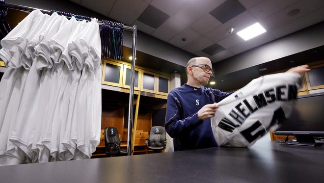 Seattle Mariners clubhouse assistant Pete Fortune begins to fold a jersey of former relief pitcher Tom Wilhelmsen, who was traded to the Texas Rangers, as he packs equipment bound for spring training, Wednesday, Feb. 10, 2016, in Seattle. Because the white jerseys are only used for photo day, outdated jerseys can be re-used. Fortune, a 30-year team employee, said the turnover of players on the club from the previous season is the most that he recalls ever seeing. Team personnel loaded a moving van with baseball gear Wednesday morning to be shipped to the team's training facility in Peoria, Ariz. Pitchers and catchers begin working out Feb. 20. Position players begin the first full squad workout Feb. 25.