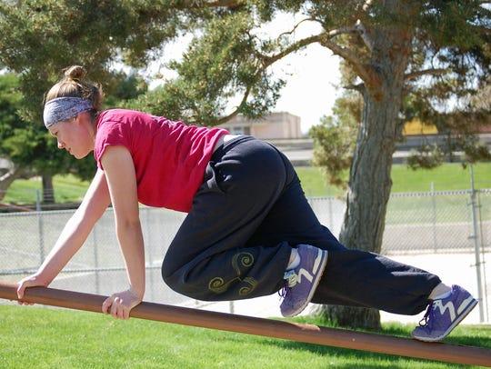 Natalie Kreil crawls along a rail on April 23 while