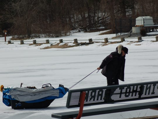 An ice fisherman drags his sled from the lake at Pinchot State Park.