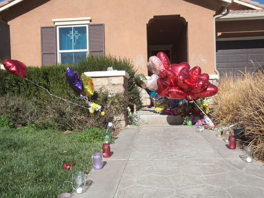 Candles and balloons stand outside a Perris, Calif.,