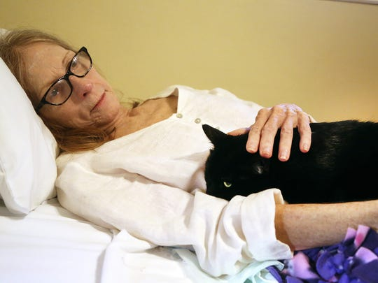 Joan Price, 65, who is dying from liver damage, gets a visit from her 21/2-year-old cat, Isis, at her assisted-living facility in Hollywood, Fla. Isis is being fostered by Leslie Wynne, who brings Isis once or twice a week to the home.