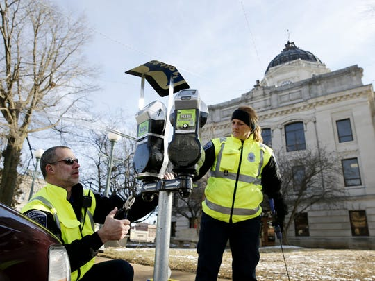 Parking enforcement officers Ross Jackson and Susan McCarter install covers made from old city street sign to keep crow feces from falling on the parking meters around the Monroe County Courthouse in Bloomington.