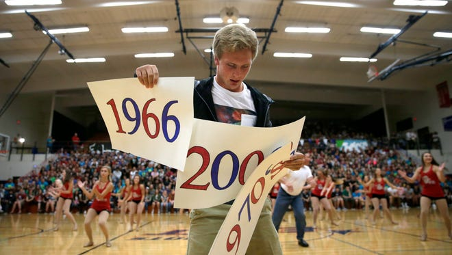 Cade Ritchie, a junior at Appleton East High School, gets ready to hold the 1970 sign in the air during a performance by the dance team which included five staff members who represented the decades East has been in existence during a pep rally celebrating the first day of school and East's 50th anniversary Thursday, Sept. 1, 2016.