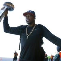 Cornerback Chris Harris shows off the Lombardi Trophy as the Broncos arrive back in Denver following their Super Bowl 50 victory.