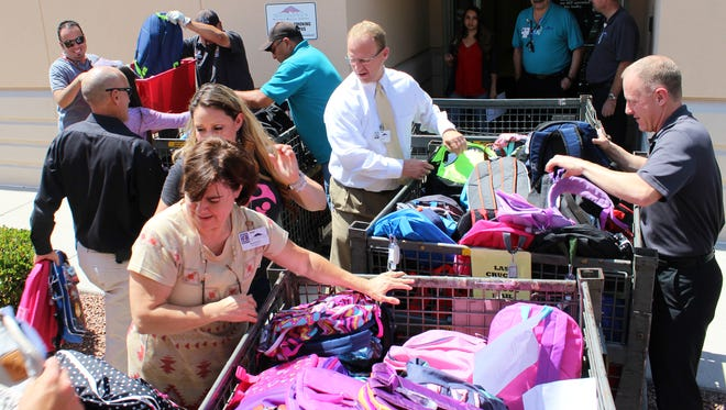 Employees from Las Cruces Public Schools and MountainView Regional Medical Center help load 410 backpacks filled with school supplies into sorting bins. MVRMC donated the backpacks to Las Cruces Public Schools, Friday, Aug. 4.