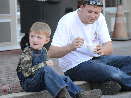 Koty Gean (right) and his step-son Christian Brouillette, 4, try some of the foods created at the United Way Wild Cook-Off on Thursday.