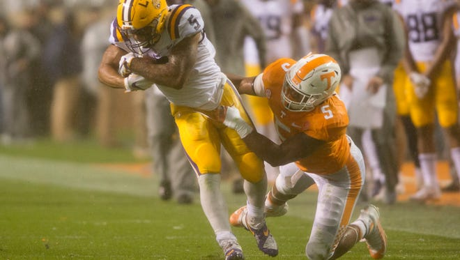 LSU running back Derrius Guice (5) runs the ball while Tennessee defensive lineman Kyle Phillips (5) tries to tackle him during a game between Tennessee and LSU at Neyland Stadium in Knoxville, Tennessee, on Saturday, Nov. 18, 2017.