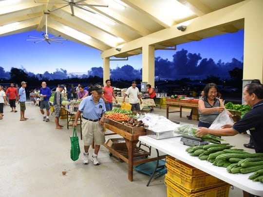In this file photo, early-morning shoppers beat the heat and the crowds at the grand opening of the Dededo flea market on Dec. 10, 2016.