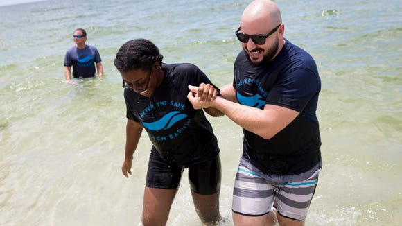 "Troy Maragos, Pastor of College and Twenties Ministries at First Baptist Church, helps Nathalie Faugue out of the water after baptizing her amongst friends, family, and other members of the congregation during a beach baptism ceremony at La Mer Condominiums Sunday, August 6, 2017 in Naples. Faugue, 19, said it was an easy choice to decide who would baptize her. ""I wouldn't want anyone else,"" she said."