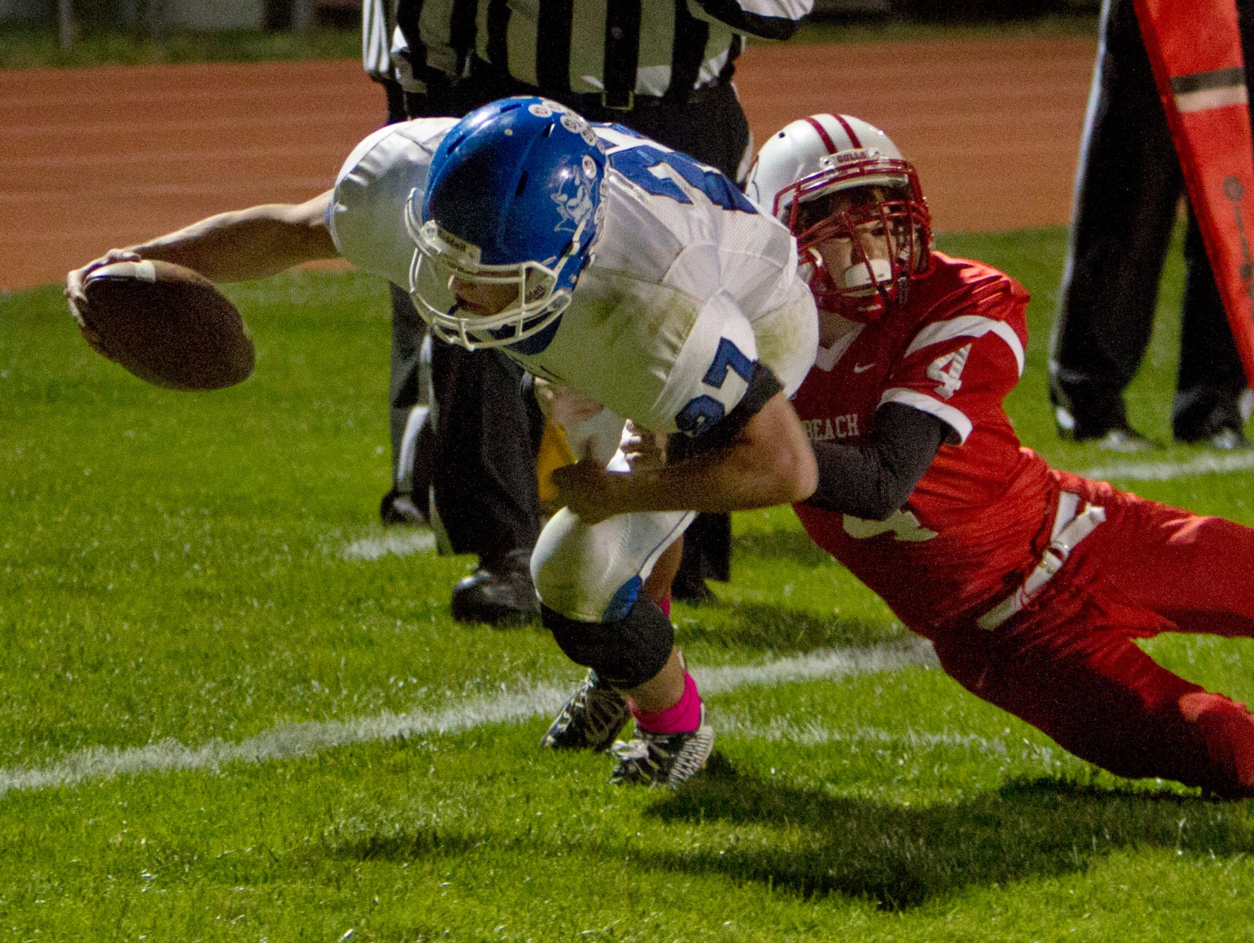 Shore Regional's Jack Britton stretches out but can't quite got to the goal line as Pt Beach's Josh Yates hangs on to him, but did pick up yards that let his team score a second time two plays later. Shore Regional football vs Point Pleasant Beach in Point Pleasant Beach on October 30, 2015.