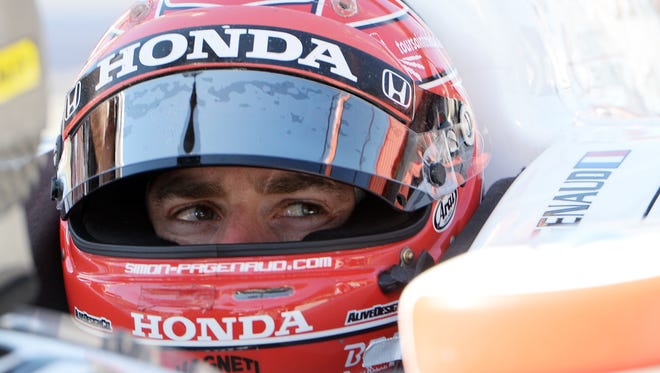 Simon Pagenaud sits in his race car as he waits for practice for Saturday's Indycar auto race Friday, Aug. 29, 2014, at Auto Club Speedway, in Fontana, Calif.